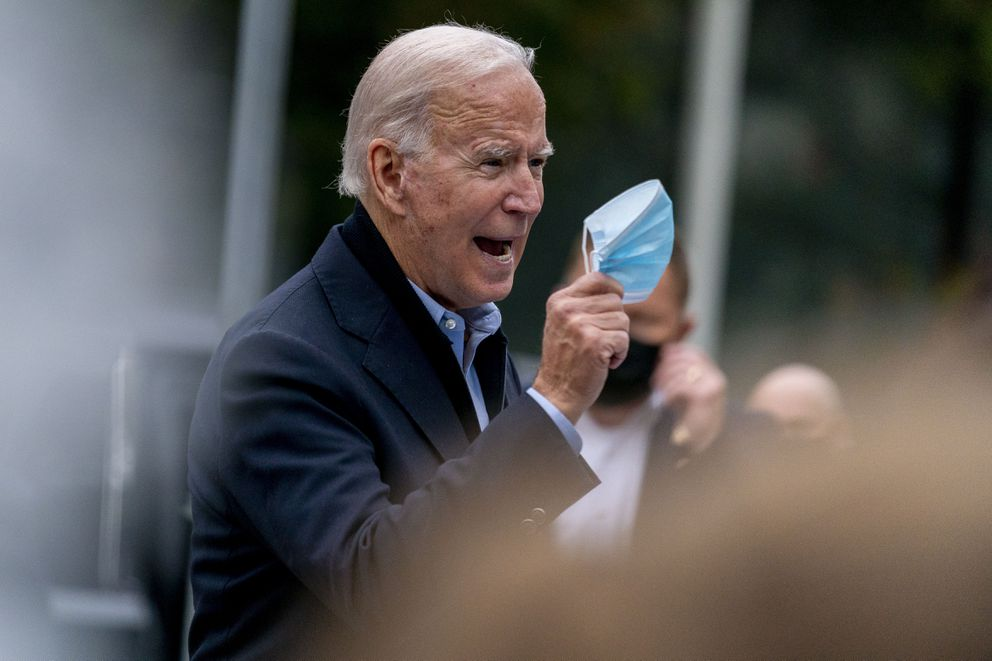 Democratic presidential candidate former Vice President Joe Biden holds up his face mask as he speaks to members of the media outside a voter service center, Monday, Oct. 26, 2020, in Chester, Pa. (AP Photo/Andrew Harnik)