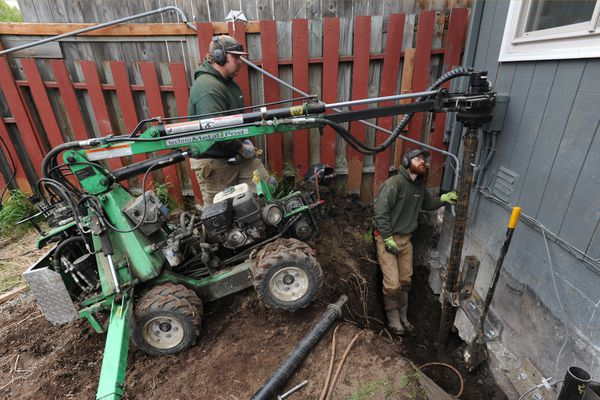Jason Macrander and Tim Weise of Techno Metal Post Alaska install a helical pier while lifting and stabilizing an earthquake-damaged home in West Anchorage on Thursday, May 16, 2019. (Bill Roth / ADN)