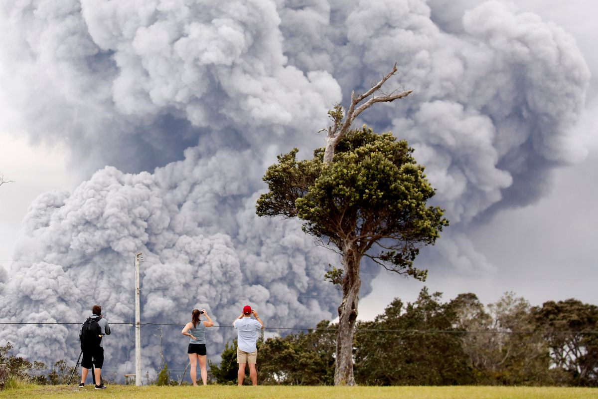 People watch Tuesday as ash erupts from the Halemaumau crater during ongoing eruptions of the Kilauea volcano in Hawaii. REUTERS/Terray Sylvester