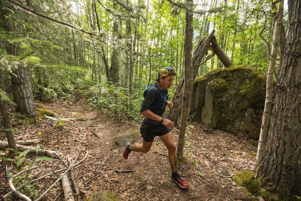 Zach Miller runs past a glacial erratic. (Loren Holmes / ADN)