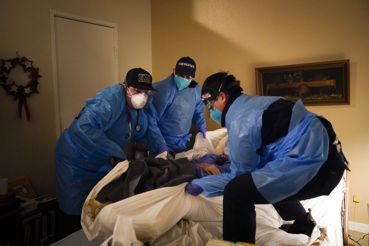 Emergency medical workers lift a patient onto a gurney in Placentia, Calif., Saturday, Jan. 9, 2021. (AP Photo/Jae C. Hong)
