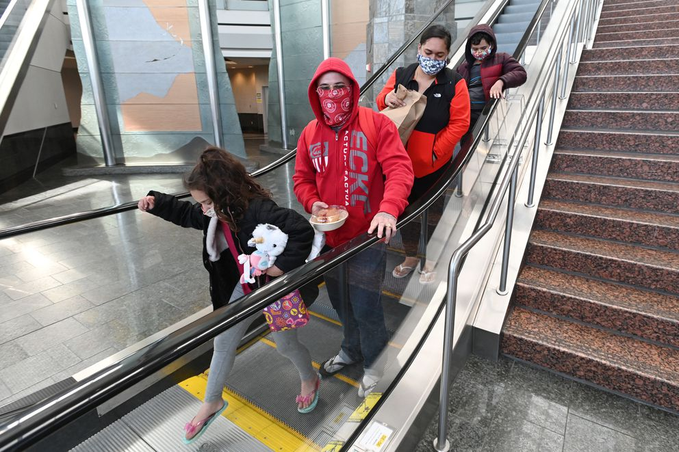 Anne Fischer, 7, her father Jonathon Fischer and mother Koleta Maalona-Fischer and brother Amor Fischer, 8, wear masks after arriving to Ted Stevens Anchorage International Airport on Sunday, May 3, 2020, after traveling all night from Hawaii to Seattle to Anchorage during the COVID-19 pandemic. (Bill Roth / ADN)