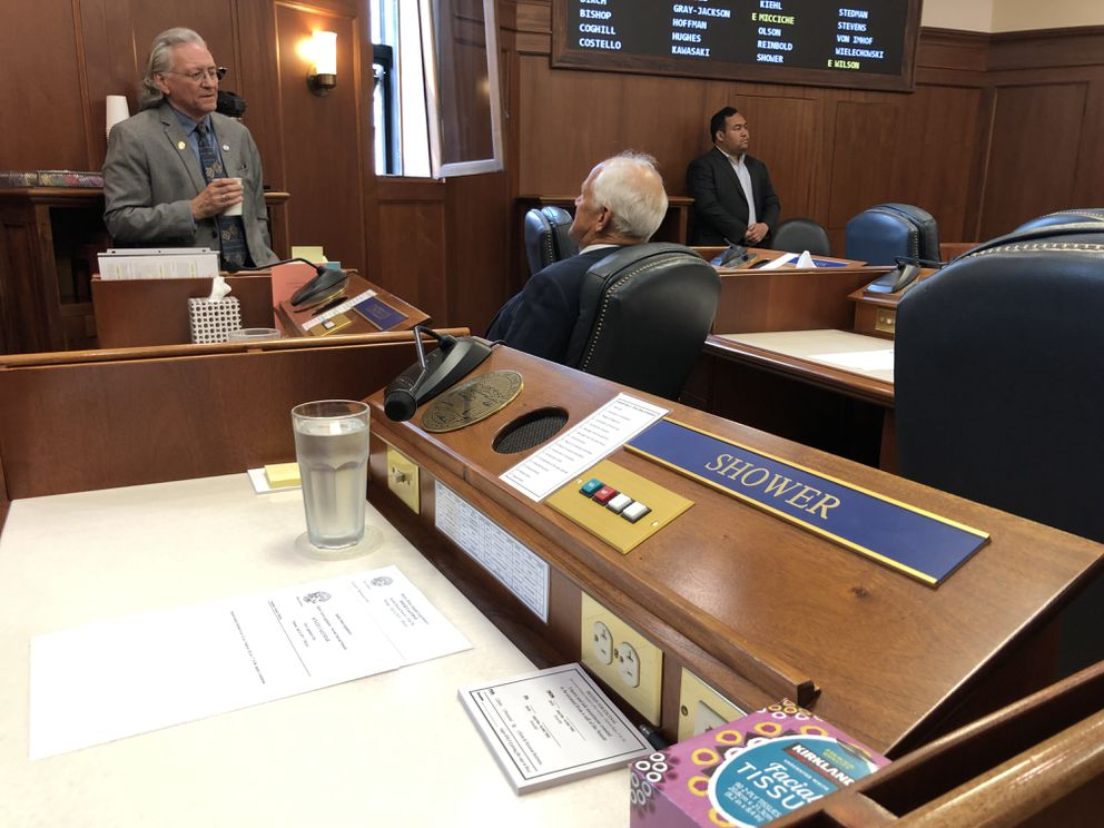 The Alaska Senate seat of Sen. Mike Shower, R-Wasilla, sits vacant Monday, July 8, 2019 as the second special session of the 31st Alaska Legislature begins. At background are (at left) Senate Minority Leader Tom Begich, D-Anchorage, and (seated) Sen. Chris Birch, R-Anchorage. (James Brooks / ADN)