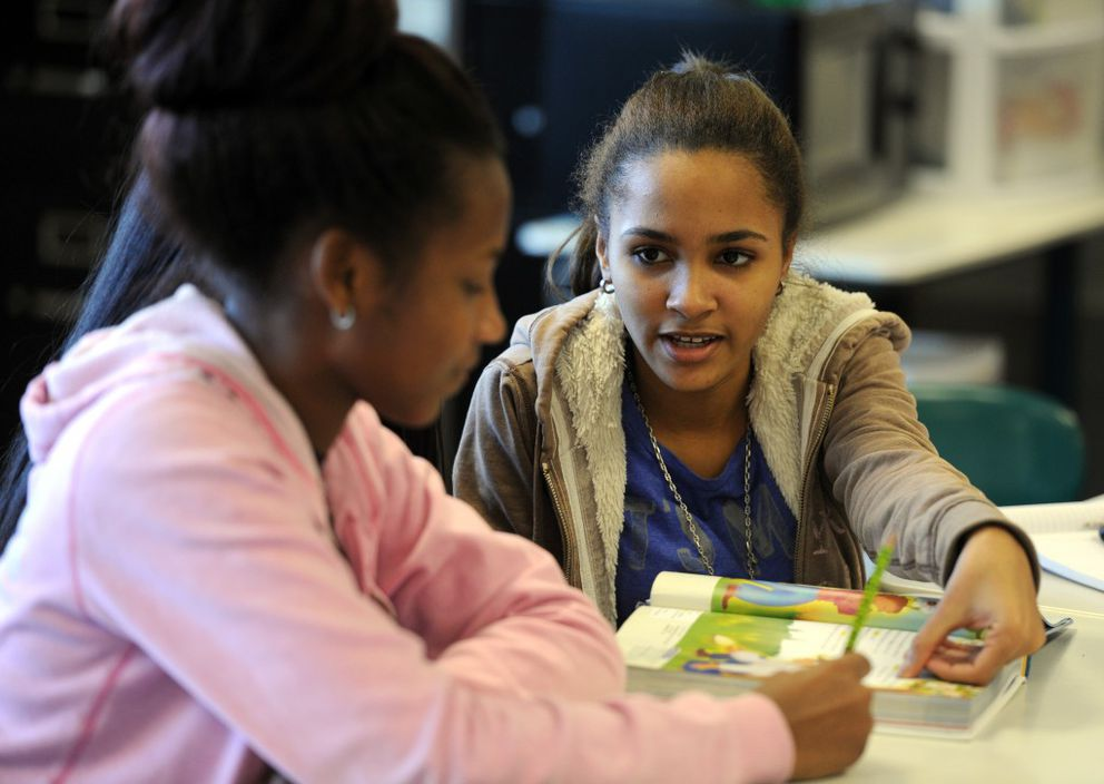 Kismairy Garcia from the Dominican Republic, right, helps a new student in Bonnie Palach's class on Sept. 30 at Wendler Middle School. (Erik Hill / Alaska Dispatch News)