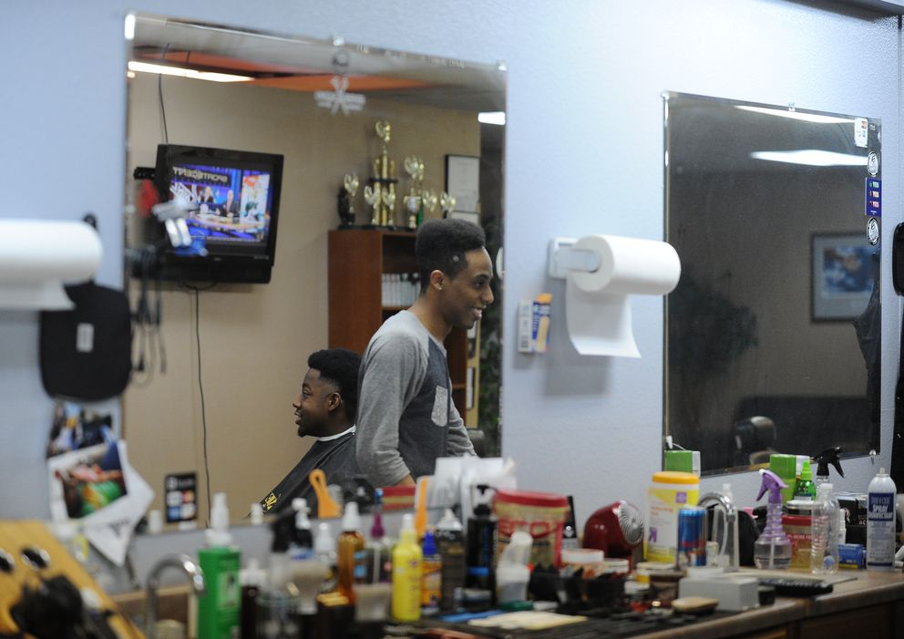 Anthony Squalls has his hair cut by Marcus Freeman at Unique Blends on Muldoon Road on Tuesday, Aug. 2, 2016, in Anchorage. Reflected in the mirror are barber competition trophies mostly won by Freeman. (Bob Hallinen / Alaska Dispatch News)