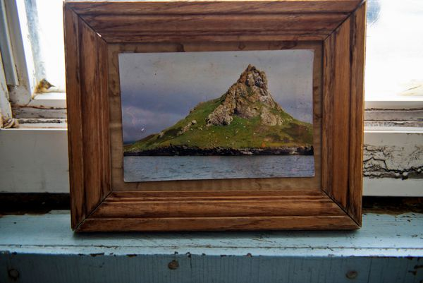 In Joe Akeya's home his displays a photo of Punuk Island, a small island off the eastern end of St. Lawrence Island, where he goes to dive. (Marc Lester / Alaska Dispatch News)