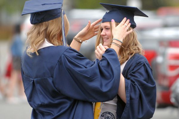 Ashton McCluskey helps fellow graduate Addison Swanson with her graduation cap before commencement ceremonies for Eagle River High School on Wednesday, May 15, 2019 at Sullivan Arena in Anchorage. (Matt Tunseth / Chugiak-Eagle River Star)