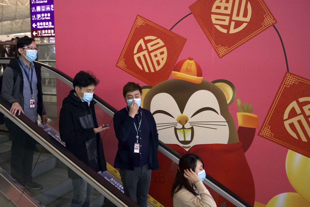 People wear face masks as they ride an escalator at the Hong Kong International Airport in Hong Kong, Tuesday, Jan. 21, 2020. Face masks sold out and temperature checks at airports and train stations became the new norm as China strove Tuesday to control the outbreak of a new coronavirus that has reached four other countries and territories and threatens to spread further during the Lunar New Year travel rush. (AP Photo/Ng Han Guan)