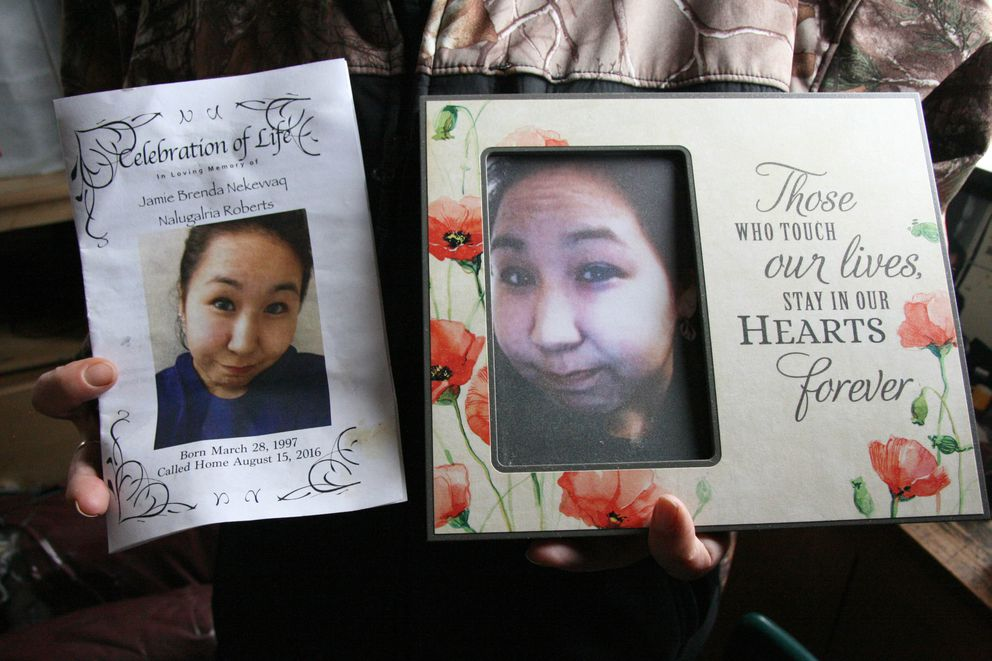 Phyllis Roberts of Quinhagak on Sept. 15, 2016, is holding a photo of and the memorial service flier for her daughter, Jamie Brenda Nekevv Roberts, who died a month earlier of a heroin overdose in the Southwestern Alaska village.