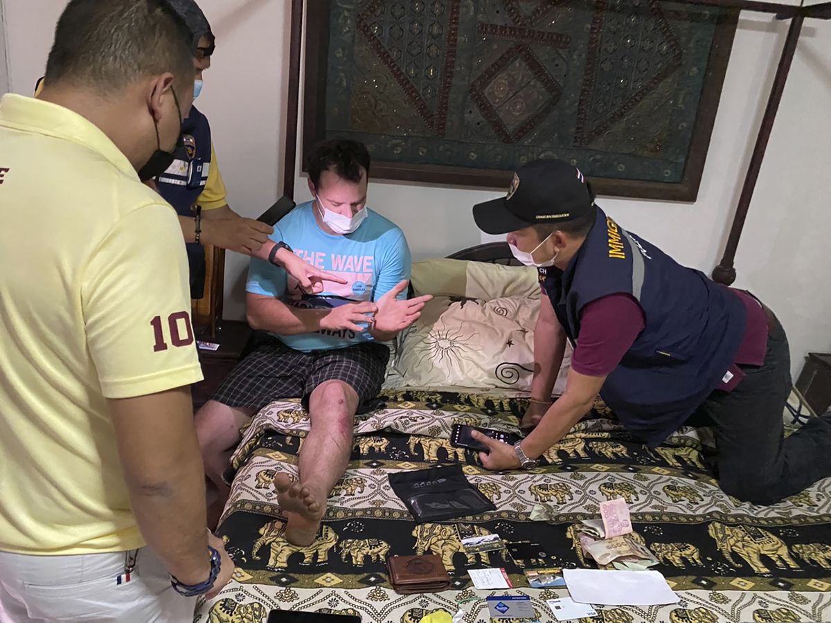 In this Thursday, May 6, 2021, photo released by the Thai Provincial Police Region 5, police arrest and interrogate American citizen Jason Matthew Balzer, center, in Chiang Mai province northern Thailand before charging him for intentionally murdering his pregnant wife in Nan province. (Thai Provincial Police Region 5 via AP)