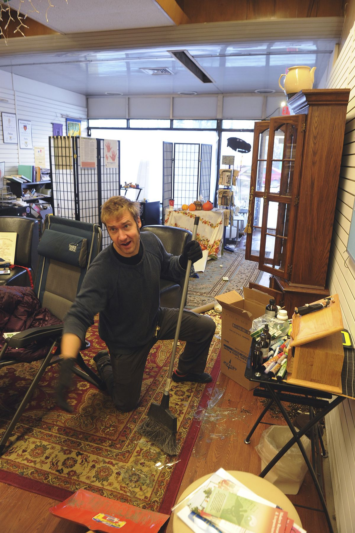 Tristan Cobine helps clean up broken glass in the offices of the Institute Alaska, following an earthquake, Friday, Nov. 30, 2018, in Anchorage, Alaska. (AP Photo/Michael Dinneen)
