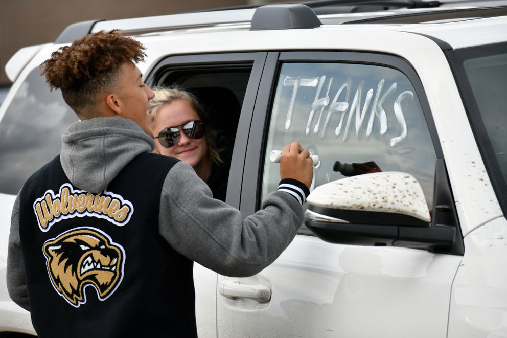"""South High School football player Kellen Curtis writes """"Thanks ASD"""" on a vehicle before it departs from the school parking lot for a drive-by demonstration at Anchorage School District headquarters. On Thursday, ASD announced that sports teams can resume full practices. (Marc Lester / ADN)"""