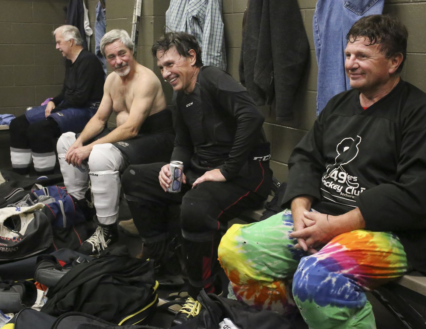 Steve Carlson, center, sits with teammates and sips a cold beer after a hockey game. Don Carlson, right, wears the tie-dye pants Steve has kept in his hockey bag for more than 20 years to loan to players who forget theirs. Don wore them after forgetting his pants for a recent game. (Emily Mesner / ADN)