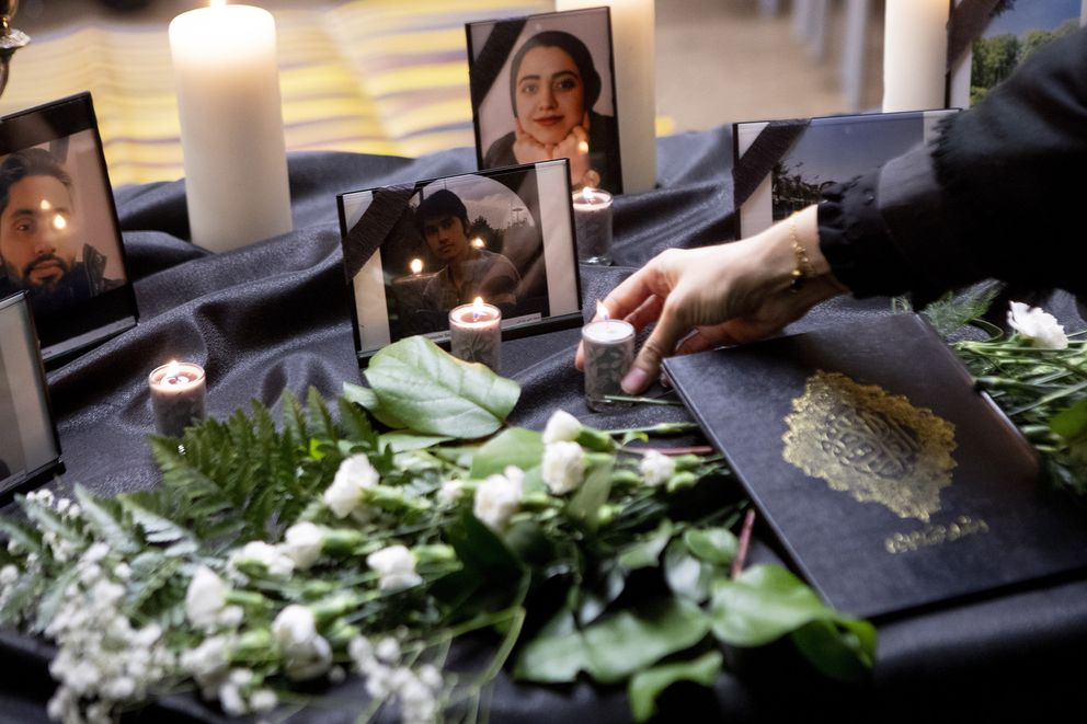 A candle is placed on a table bearing photos of some of the victims of a Ukraine International Airlines passenger flight that crashed after takeoff near Tehran, Iran, as members of Toronto's Iranian community attend a vigil in Toronto, Wednesday, Jan. 8, 2020. (Chris Young/The Canadian Press via AP)