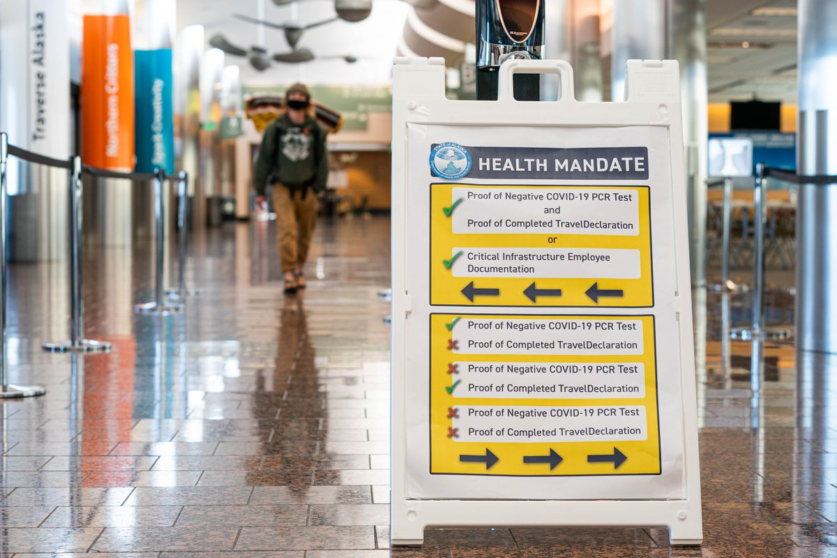 A person walks past a sign explaining new a new state health mandate requiring COVID-19 testing for travelers entering Alaska on Friday, June 5, 2020 in the B Concourse at the Ted Stevens Anchorage International Airport. Screening will begin at the airport at midnight. (Loren Holmes / ADN)