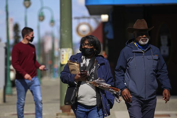 Rosa and Harold Meadors, visiting from Seattle, cross W. Fourth Avenue in downtown Anchorage on Thursday, May 13, 2021. (Emily Mesner / ADN)
