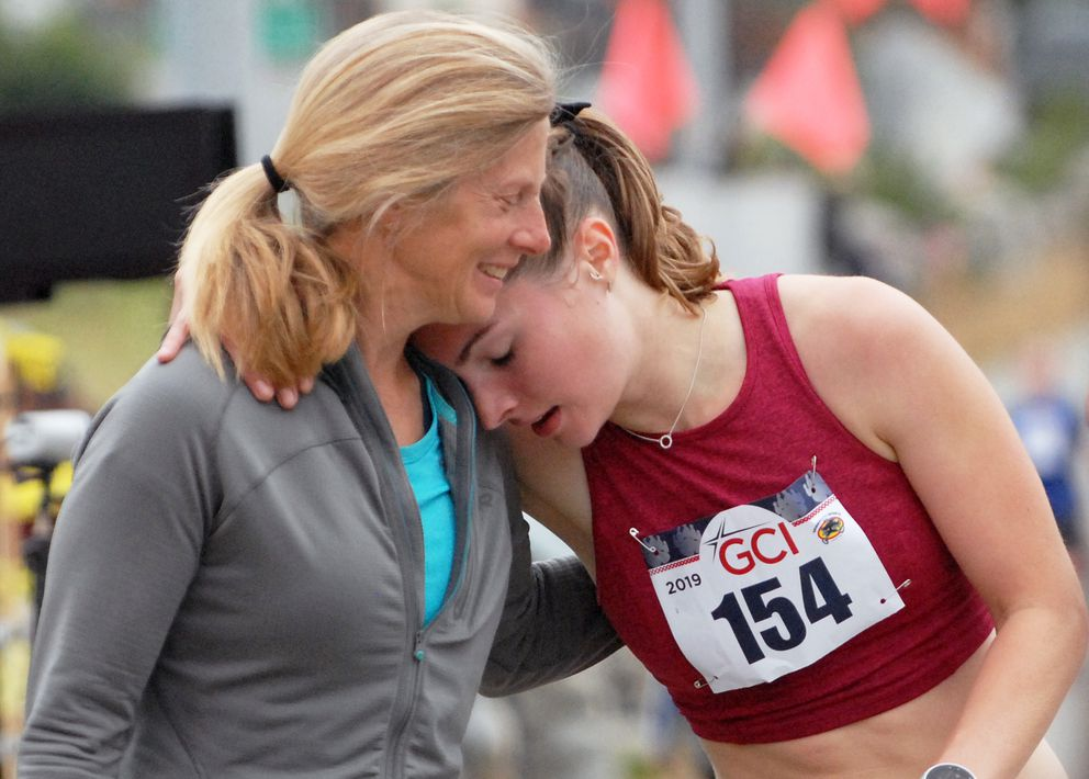 Susan Casey, left, hugs Bear Paw 5K winner Hannah Booher after Booher won the race in 19 minutes Saturday, July 13, 2019. (Matt Tunseth / Chugiak-Eagle River Star)