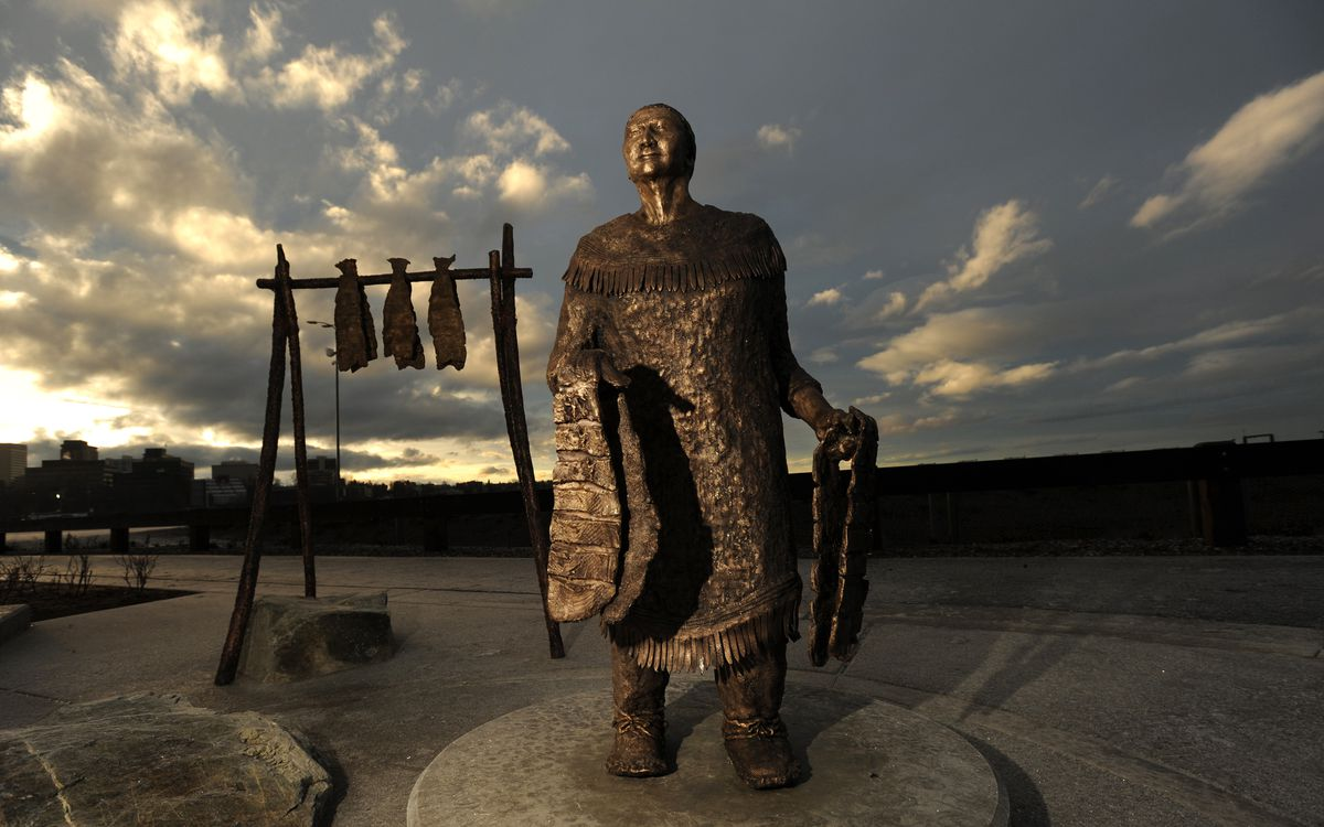 Morning sunlight illuminates clouds behind the bronze sculpture of Grandma Olga Nikolai Ezi. (Bill Roth / ADN)