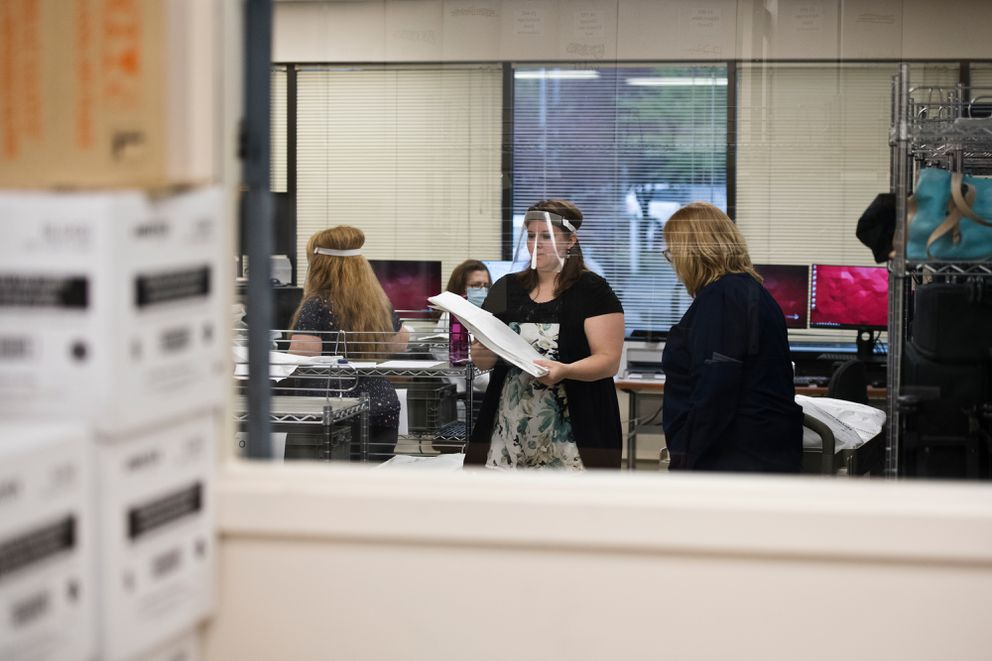 Beth Madren, center, works in a Division of Elections ballot counting room in Anchorage on August 25, 2020. (Marc Lester / ADN)