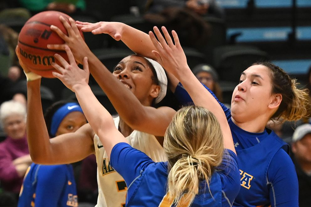 UAA junior guard Lauren Johnson draws a crowd as she drives to the basket. (Bill Roth / ADN)