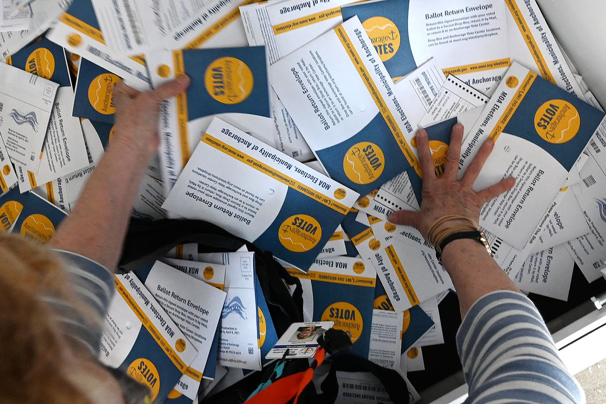 Election worker Karen Ingraham gathers ballot envelopes from inside a secure drop box at the Eagle River Town Center that were taken to the MOA Election Center during the regular municipal election on Tuesday, April 6, 2021. (Bill Roth / ADN)