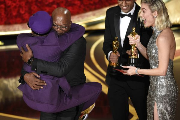 Samuel L. Jackson, center left, embraces Spike Lee, winner of the award for best adapted screenplay for