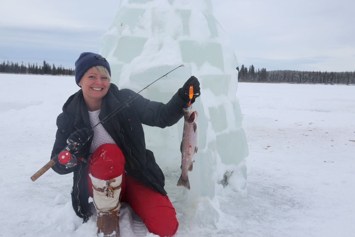 Christine Cunningham holds up a rainbow trout caught on a Kenai Peninsula lake. Behind her is an ice house left behind by other anglers. (Photo by Steve Meyer)