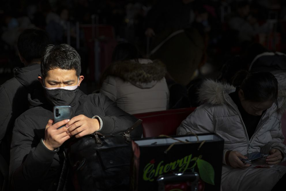 A traveler wears a face mask as he sits in a waiting room at the Beijing West Railway Station in Beijing, Tuesday, Jan. 21, 2020. A fourth person has died in an outbreak of a new coronavirus in China, authorities said Tuesday, as more places stepped up medical screening of travelers from the country as it enters its busiest travel period. (AP Photo/Mark Schiefelbein)