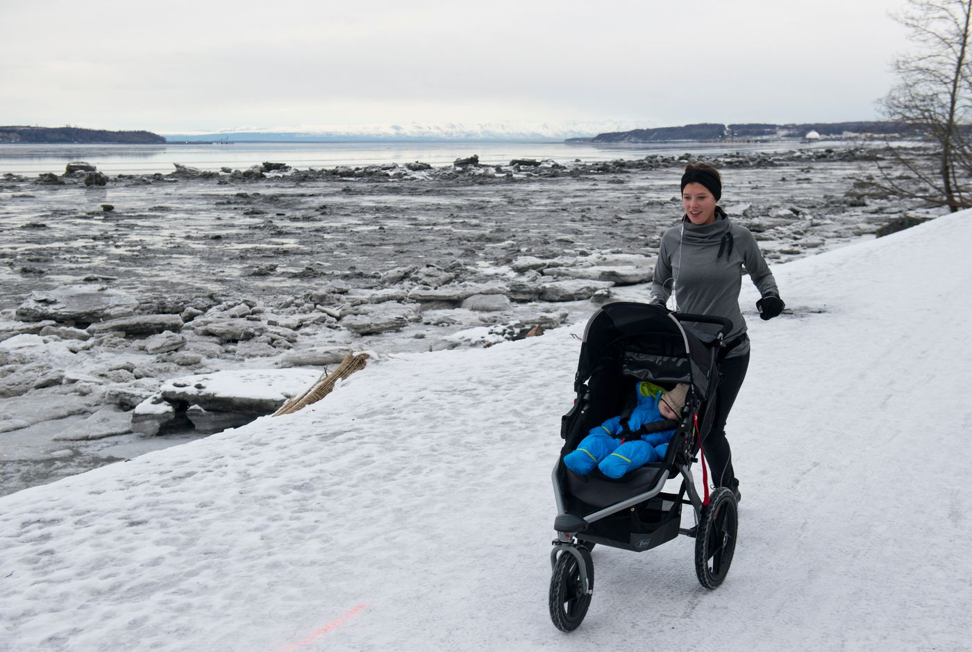 Pushing her son in front of her, Sabrina Walker runs on Anchorage's Tony Knowles Coastal Trail on Thursday, February 11, 2016.