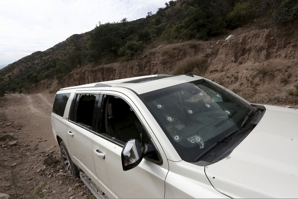 A bullet-riddled vehicle that members of LeBaron family were traveling in sits parked on a dirt road near Bavispe, at the Sonora-Chihuahua border, Mexico, Wednesday, Nov 6, 2019. Three women and six of their children, related to the extended LeBaron family, were gunned down in an attack while traveling along Mexico's Chihuahua and Sonora state border on Monday. (AP Photo/Christian Chavez)