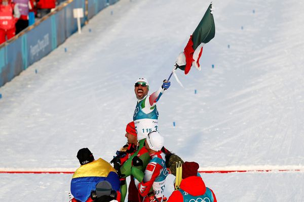 Cross-Country Skiing - Pyeongchang 2018 Winter Olympics - Men's 15km Free - Alpensia Cross-Country Skiing Centre - Pyeongchang, South Korea - February 16, 2018 - German Madrazo of Mexico holds the Mexican flag after crossing the finish line. REUTERS/Murad Sezer SEARCH