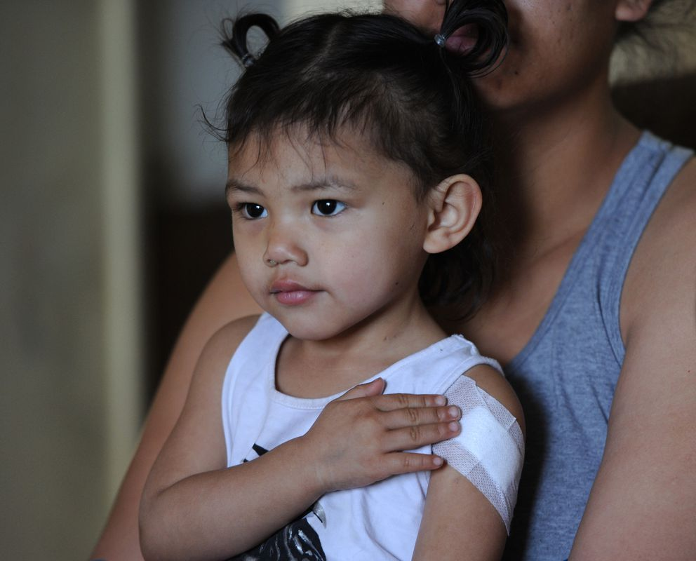 Kuulei Steele holds her two-year-old daughter Kapua Murphy in May after the child was shot in their Fairview home. (Bill Roth / ADN)
