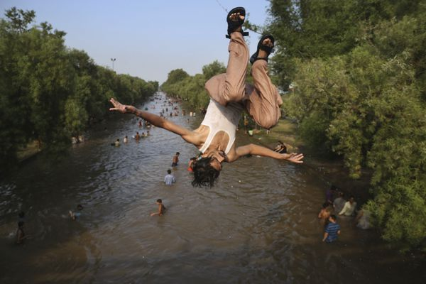 A Pakistani jumps as people cool themselves off in a canal in Lahore, Pakistan, where temperature reached 44 degrees Celsius (111 Fahrenheit), Sunday, June 2, 2019. Many cities in Pakistan are facing heat wave conditions with temperatures reaching 49 degrees Celsius (120.2 Fahrenheit) in some place. (AP Photo/K M Chaudhry)