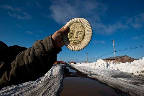 Dean Kulowiyi holds a piece of his artwork he was selling in Savoonga on April 19. Kulowiyi, like many residents of the St. Lawrence Island village, carves ivory and bone. (Marc Lester / Alaska Dispatch News)