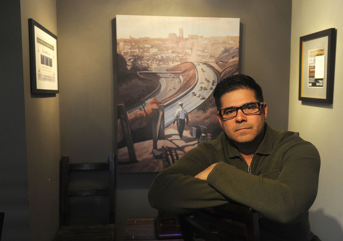 """Anchorage firefighter,paramedic and author Bryan Fierro has just published the novel """"Dodger Blue will Fill Your Soul."""" The print behind him shows Chavez Ravine in Los Angeles, the setting for part of his book. Photographed at his Anchorage home on Friday, Oct. 20. (Bob Hallinen / Alaska Dispatch News)"""