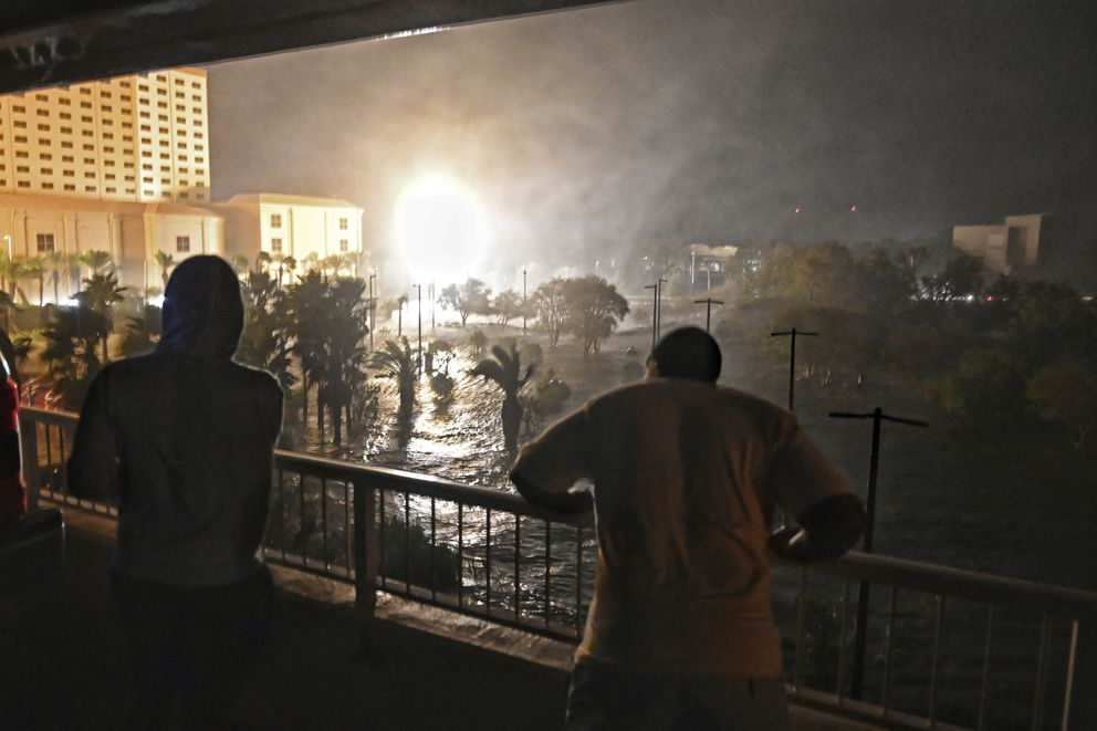 Patrons of the Golden Nugget Biloxi Casino and Resort in Biloxi, Miss., look out at the storm surge as it floods the first floor of their parking garage, Wednesday night, Oct. 28, 2020, as Hurricane Zeta made landfall on Mississippi's Gulf Coast. (Lukas Flippo /The Sun Herald via AP)