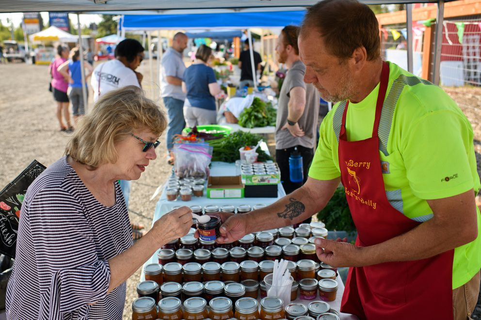 Customer Edie Elmore tastes a product from Ted Stumo's Alley Berry stand at Grow North Farm's monthly market. (Marc Lester / ADN)