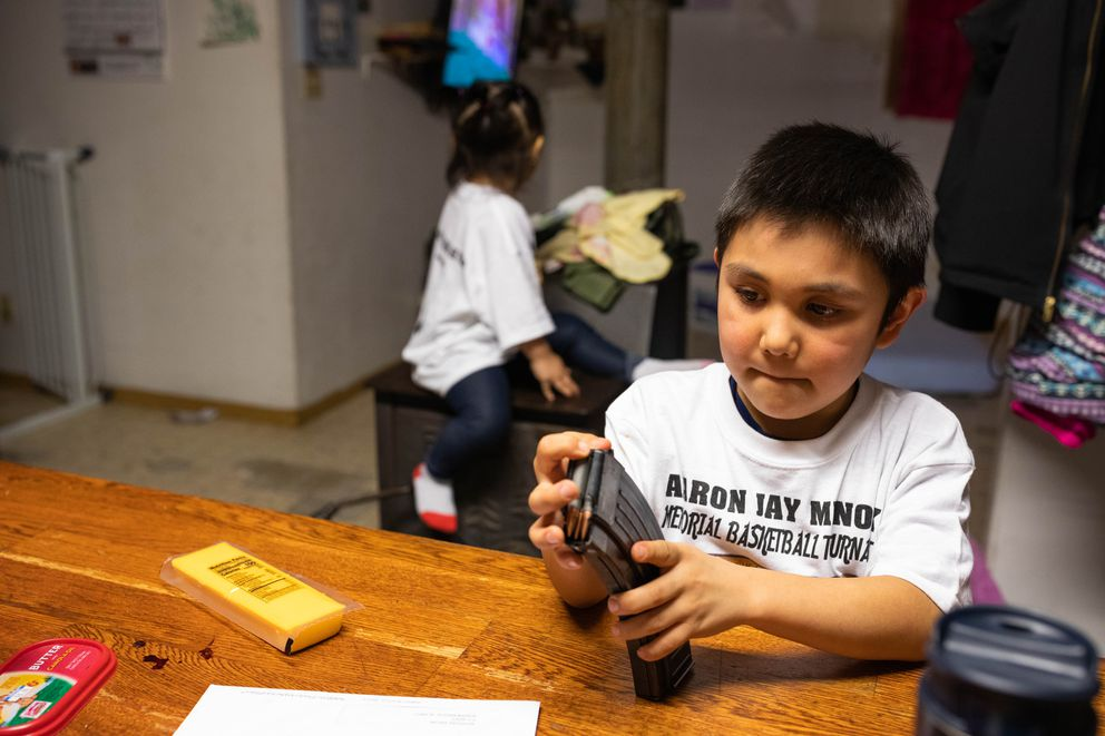 Blake Askoak, 5, plays with a rifle clip at his kitchen table. (Loren Holmes / ADN)