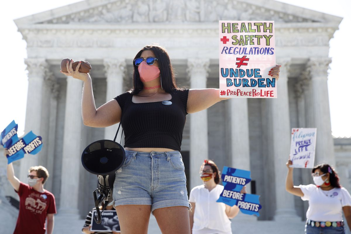 Terrisa Bukovinac, founder of Pro-Life San Francisco, holds a model of a fetus as she and other anti-abortion protesters wait outside the Supreme Court for a decision, Monday, June 29, 2020. The Supreme Court has struck down a Louisiana law regulating abortion clinics, reasserting a commitment to abortion rights over fierce opposition from dissenting conservative justices in the first big abortion case of the Trump era. (AP Photo/Patrick Semansky)