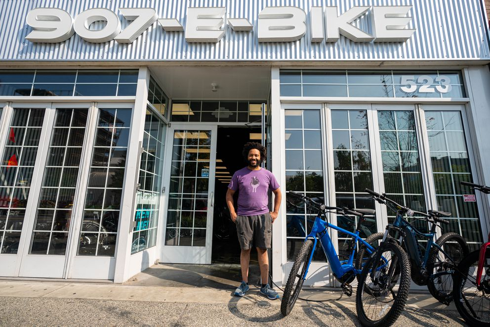 907 E-Bike manager Danny Miller stands outside the downtown rental shop on Friday, July 16, 2021. (Loren Holmes / ADN)