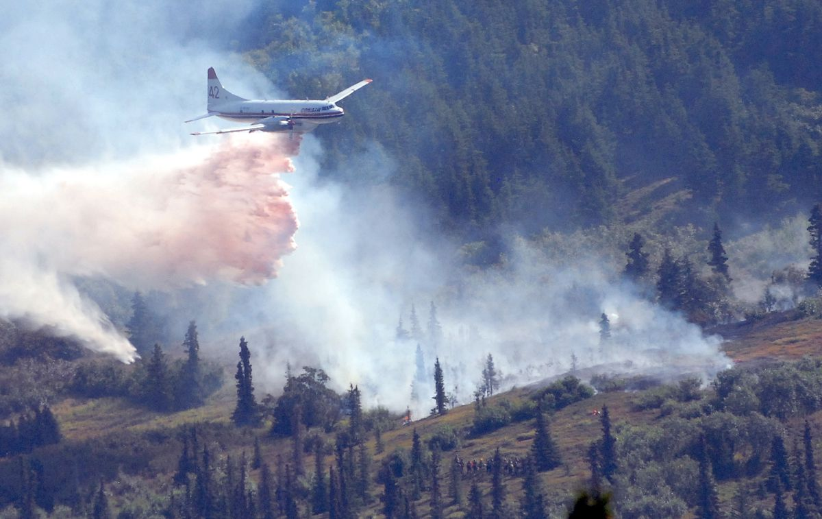 A tanker drops water-enhanced supressant on a wildfire burning on the south slope of the Meadow Creek Valley north of Eagle River on Monday, Aug. 12, 2019. At bottom right a crew of Type 2 Initial Attack wildland firefighters can be seen observing the drop. (Matt Tunseth / Chugiak-Eagle River Star)