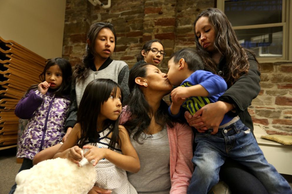 Jeanette Vizguerra kisses her youngest grandson, Santiago, 2, surrounded by her children and grandchildren in the basement of First Unitarian. Jeanette Vizguerra, 45, was seeking sanctuary at First Unitarian Society of Denver on February 15, 2017. (Washington Post photo by Alice Li)