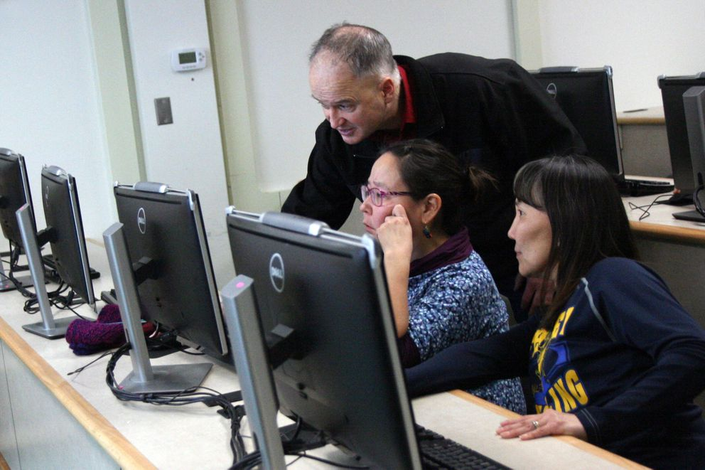 The Lower Kuskokwim School District is making a big push to create more homegrown teachers. Isabelle Dyment, right, looks on as biology professor Hector Douglas shows fellow student Kathleen Naneng a spreadsheet on plants on the Kuskokwim campus Dec. 9, 2016. Dyment is a nontraditional teacher being paid her regular salary while she goes to college full time. (Lisa Demer / Alaska Dispatch News)