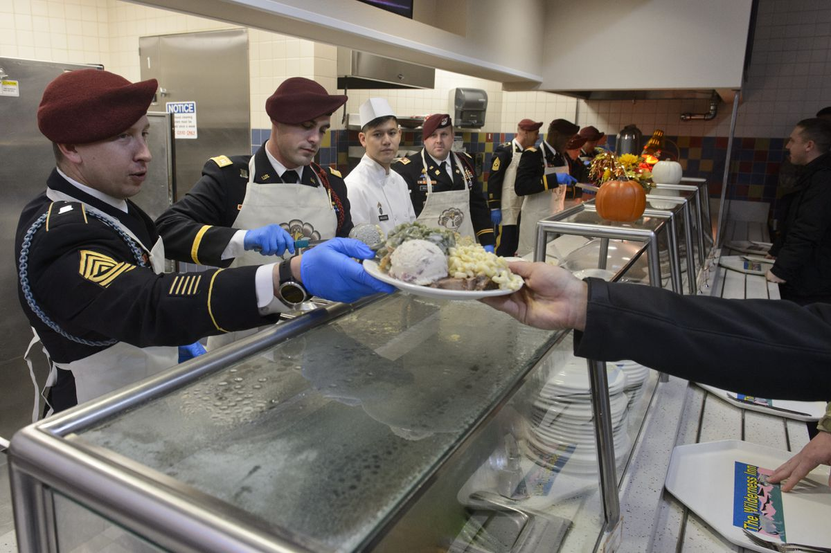 First Sgt. George Harrison hands a full plate to a soldier on Wednesday Army leadership at Joint Base Elmendorf-Richardson donned aprons to serve a Thanksgiving meal to hundreds of soldiers at the Wilderness Dining Facility. (Marc Lester / ADN)