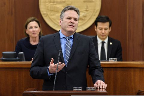 Alaska Gov. Mike Dunleavy gives his first State of the State speech to a joint session of the Alaska Legislature, Tuesday, Jan. 22, 2019, in Juneau, Alaska. Senate President Cathy Giessel, an Anchorage Republican, back left, and House Speaker Pro Tempore Neal Foster, a Nome Democrat, back right, listen to the speech, delivered in the House chamber. (Michael Penn/The Juneau Empire via AP)