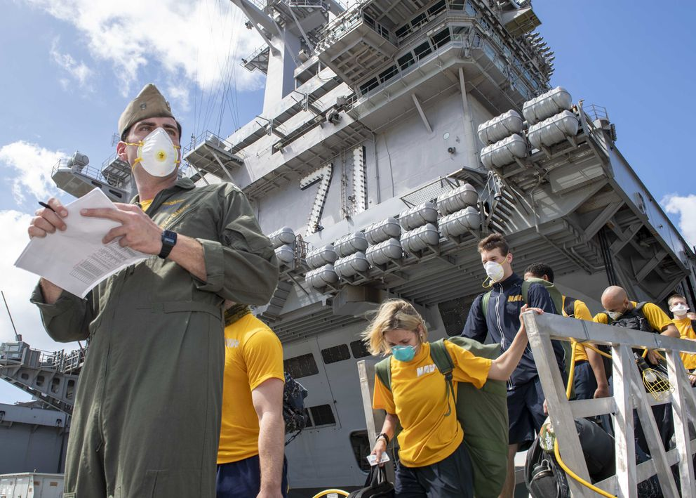 Sailors assigned to the USS Theodore Roosevelt depart the ship on April 10 to move to off-ship berthing. Christopher Liaghat/U.S. Navy.
