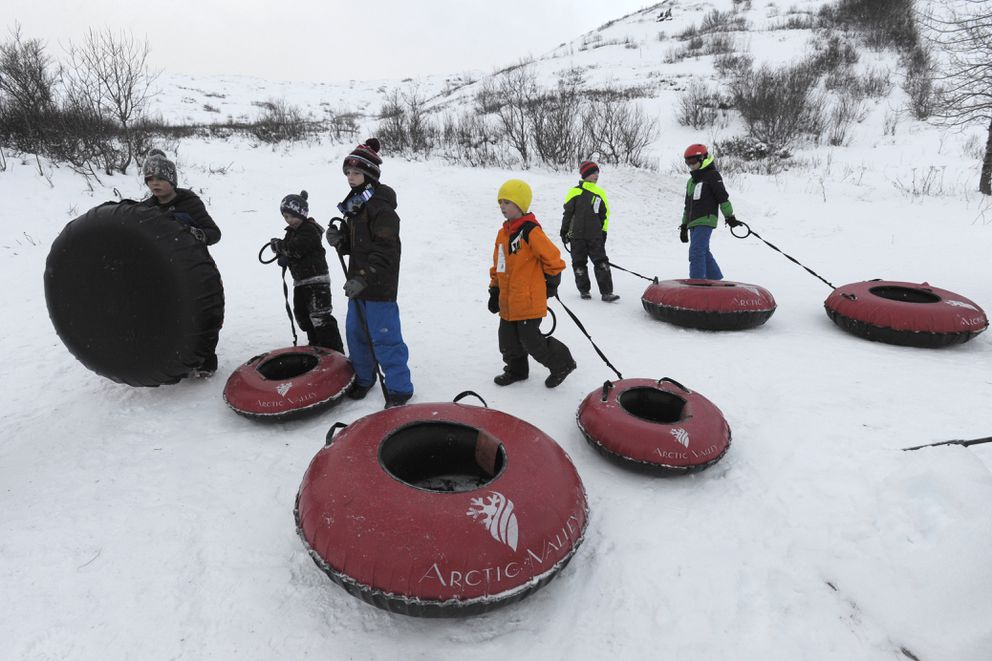 Riders wait for their turn at the top of the tube park. (Bill Roth / ADN)