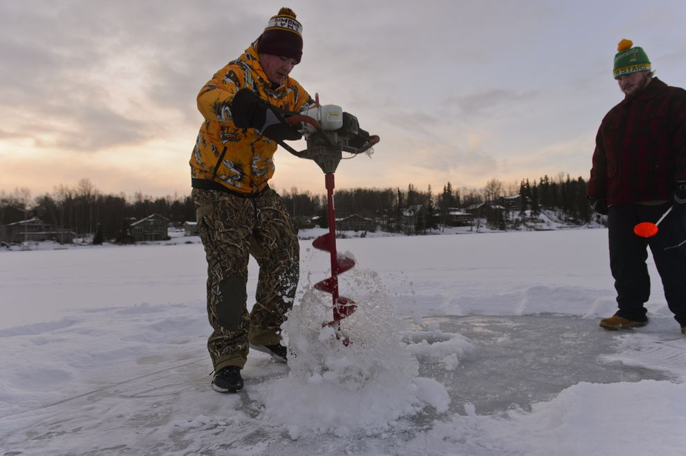 Taylor Baker uses an auger to drill a fishing hole into the ice on Sand Lake on Friday. Matthew Driskell is at right. (Marc Lester / ADN)