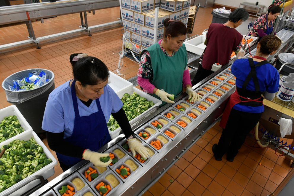Irma Ochoa places portions of broccoli into trays at the Anchorage School District's Student Nutrition facility in Anchorage on Oct. 2, 2019. The district is moving away from the use of disposable plastic covered trays and toward food that is served at the schools. (Marc Lester / ADN)