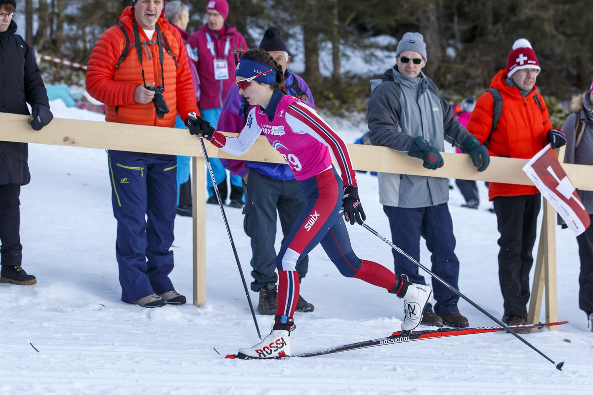Kendall Kramer skies past spectators en route to a third-place finish in the 5K classic race Tuesday at the Winter Youth Olympics In Lausanne, Switzerland. (Salvatore Di Nolfi/Keystone via AP)